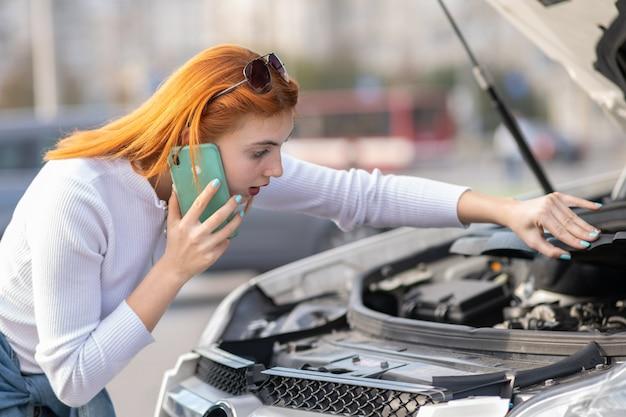 Junge frau, die nahe defektem auto mit der geknallten haube spricht an ihrem handy beim warten auf hilfe steht.