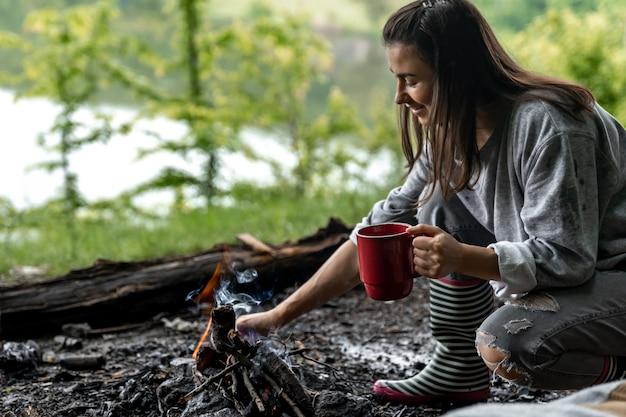 Junge frau, die nahe dem feuer mit einer tasse wärmendem getränk im wald nahe dem fluss stillsteht.