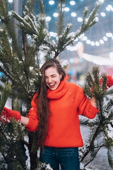 Junge frau, die nahe dem weihnachtsbaum auf der straße aufwirft
