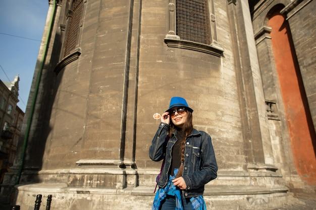 Junge frau, die nahe der kirche in der alten stadt lemberg steht. ukraine