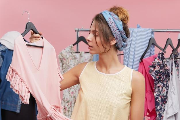 Junge frau, die nahe ihrem kleiderschrank steht, kleid auf kleiderbügeln hält und versucht, zu entscheiden, was auf party zu tragen ist. hübsche frau, die kleidung oder outfit in der umkleidekabine wählt. menschen, kleidung, modekonzept
