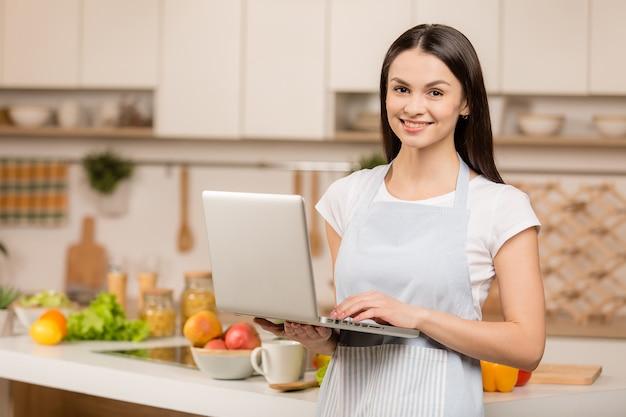 Junge frau, die nahe schreibtisch und laptop in der küche steht, lächelt und kamera betrachtet