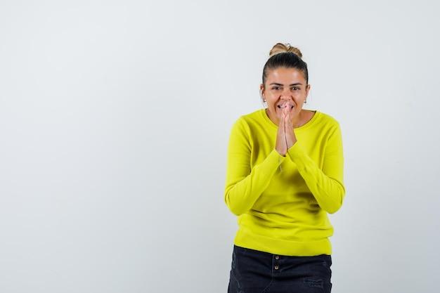 Junge frau, die namaste-geste in gelbem pullover und schwarzer hose zeigt und glücklich aussieht