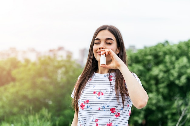 Junge frau, die nasenspray für ihre pollen- und grasallergien verwendet