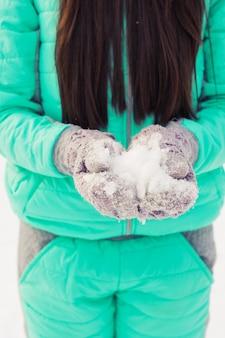 Junge frau, die natürlichen weichen weißen schnee in ihren händen hält, um einen schneeball zu machen