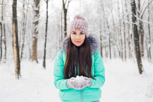 Junge frau, die natürlichen weichen weißen schnee in ihren händen hält, um einen schneeball zu machen?