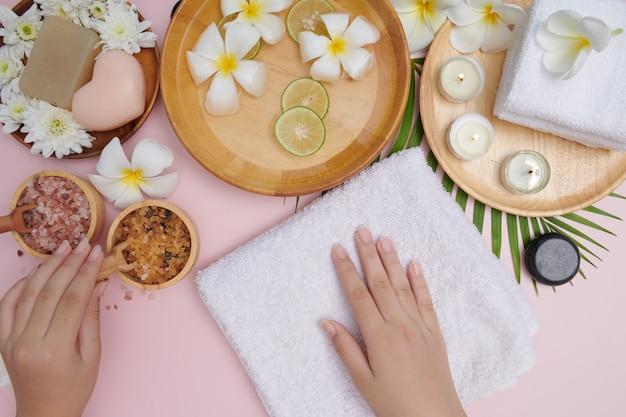 Junge frau, die natürliches peeling auf händen gegen weiße oberfläche anwendet. spa-behandlung und produkt für weibliches hand-spa, massage, parfümiertes blumenwasser und kerzen, entspannung. flach liegen. draufsicht.