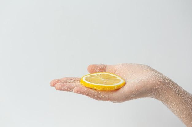 Junge frau, die natürliches zitronenpeeling auf händen gegen weiße oberfläche anwendet