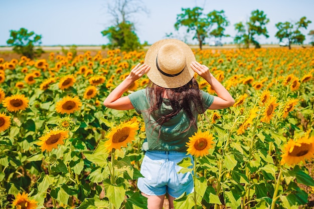 Junge frau, die natur auf dem feld der sonnenblumen genießt.