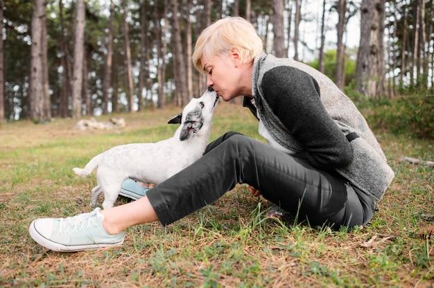 Junge frau, die natur mit ihrem hund genießt
