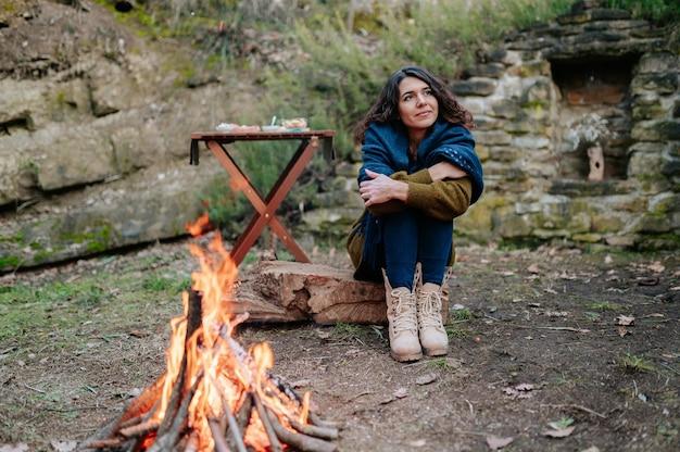 Junge frau, die neben einem feuer während eines winterpicknicks sitzt.