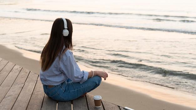Junge frau, die neben meer meditiert, während sie kopfhörer trägt