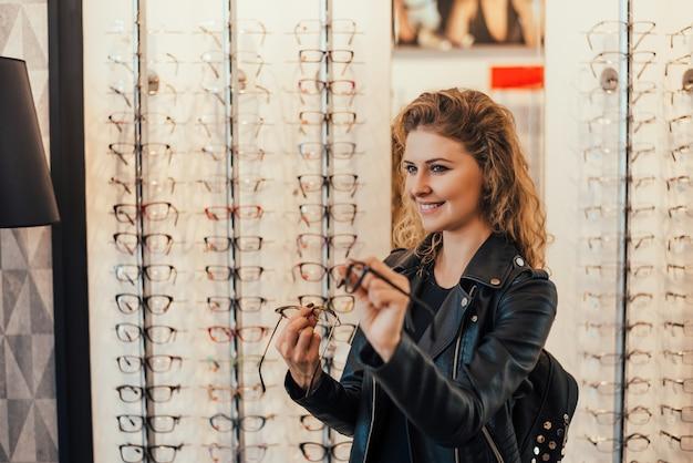 Junge frau, die neue gläser am optikerspeicher kauft.