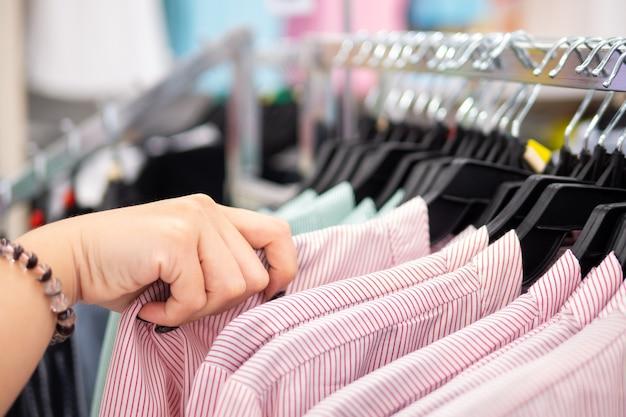 Junge frau, die neue kleidung wählt und in mode mall, abschluss oben von den händen kauft