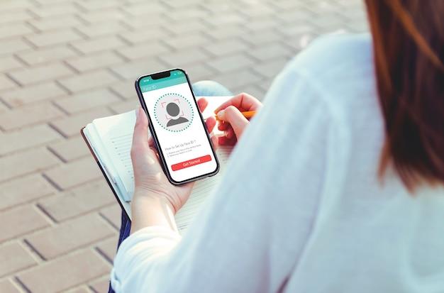 Junge frau, die neues smartphone mit gesichts-id-technologie verwendet