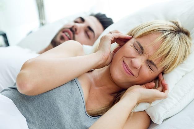Junge frau, die nicht schlafen kann, weil ihr mann schnarcht.
