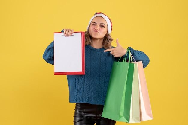 Junge frau, die notiz und pakete nach dem einkauf auf gelb hält