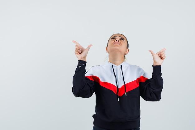 Junge frau, die oben zeigt, während sie in der vorderansicht des bunten sweatshirts fokussiert.
