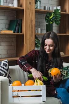 Junge Frau, die Obst und Gemüse vom Paket nimmt