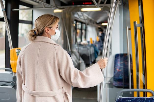 Junge frau, die öffentliche transportmittel trägt, die chirurgische maske tragen