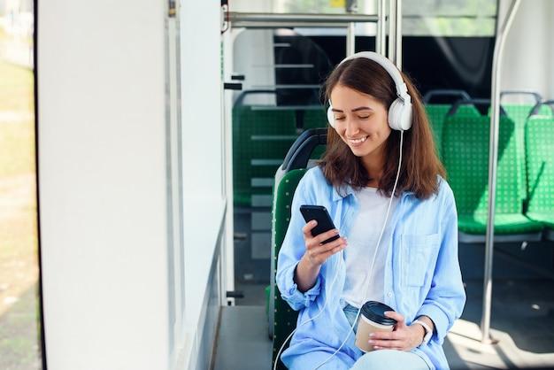 Junge frau, die öffentliche verkehrsmittel benutzt, sitzt mit smartphone und weißen kopfhörern im modernen bus.