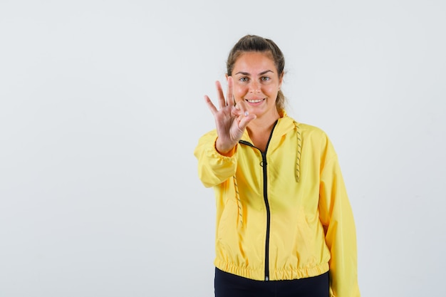 Junge frau, die ok geste im gelben regenmantel zeigt und fröhlich schaut