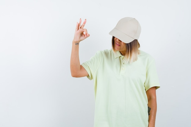Junge frau, die ok geste im t-shirt, in der mütze zeigt und zuversichtlich schaut. vorderansicht.