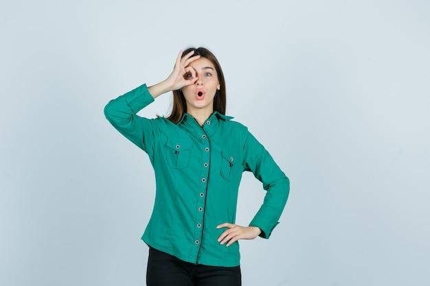 Junge frau, die ok zeichen auf auge im grünen hemd zeigt und verwundert schaut. vorderansicht.