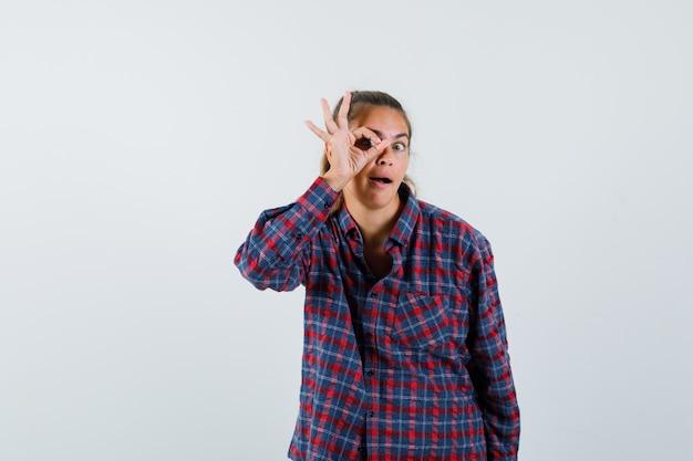Junge frau, die ok zeichen auf auge im karierten hemd zeigt und glücklich schaut