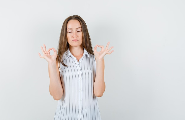 Junge frau, die ok zeichen mit geschlossenen augen im t-shirt tut und friedlich schaut. vorderansicht.