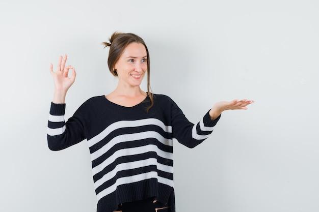 Junge frau, die ok zeichen zeigt und eine hand streckt, als etwas in gestreiften strickwaren und in schwarzen hosen hält und glücklich schaut