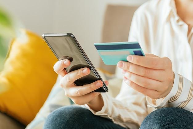 Junge frau, die online mit dem telefon und einer kreditkarte von zu hause einkauft