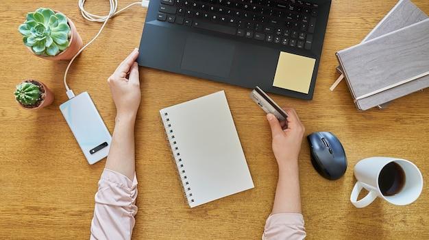 Junge frau, die online mit einer kreditkarte über einem hölzernen schreibtisch einkauft