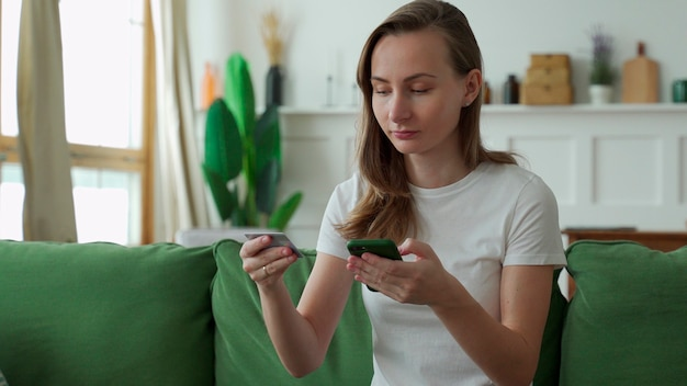Junge frau, die online mit kreditkarte und smartphone einkauft, während sie auf sofa zu hause sitzt.