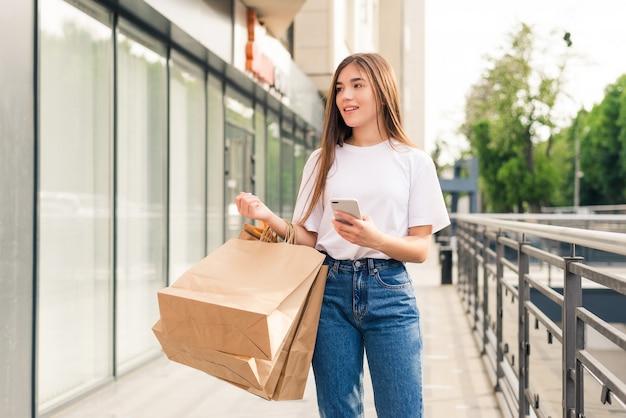 Junge frau, die online-shopping über handy macht. mädchen im modeblick, der taschen nahe schulter hält, telefon betrachtet und lächelnd auf der straße geht