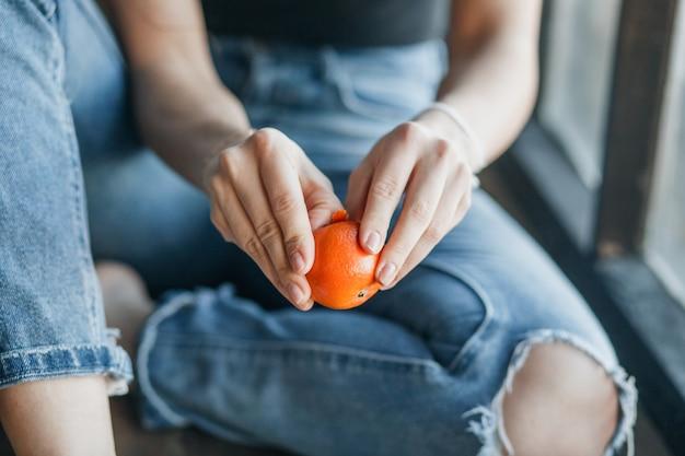 Junge frau, die orange sitzend sitzt auf der fensterbank