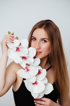 Junge frau, die orchideenblumen hält