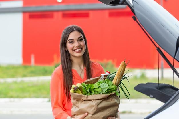 . junge frau, die paket mit lebensmitteln und gemüse in autokofferraum setzt.