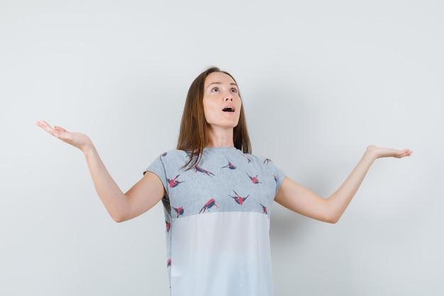 Junge frau, die palmen erhebt, während sie im t-shirt aufschaut und dankbar schaut. vorderansicht.