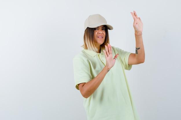 Junge frau, die palmen in der übergabegeste im t-shirt, in der mütze zeigt und hilflos schaut. vorderansicht.