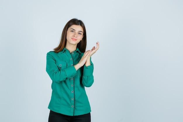 Junge frau, die palmen zusammen in grünem hemd reibt und empfindliche vorderansicht schaut.