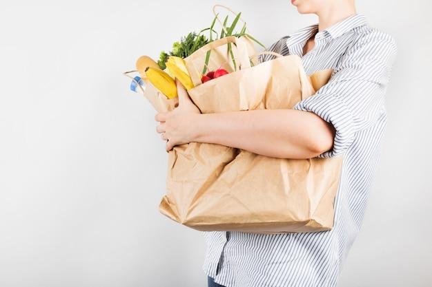 Junge frau, die papiereinkaufstaschen auf grauem hintergrund hält