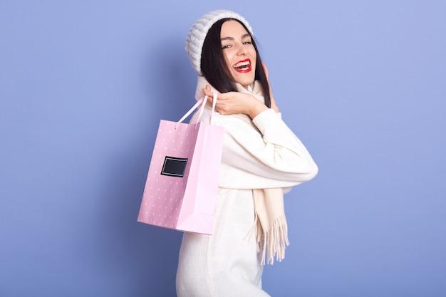 Junge frau, die papiertüte mit kauf überrascht hält, weißen pullover, mütze und schal tragend