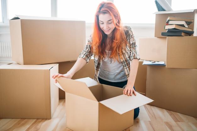 Junge frau, die pappkartons auspackt, einweihungsparty. umzug in ein neues zuhause
