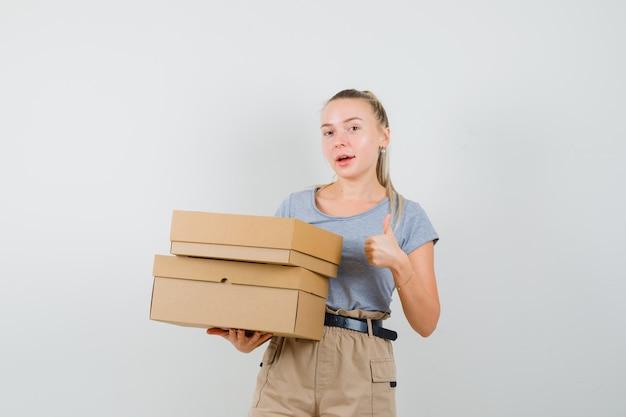 Junge frau, die pappkartons hält, zeigt daumen hoch in t-shirt, hose und schaut fröhlich. vorderansicht.