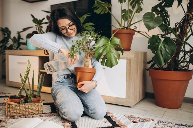 Junge frau, die pflanzen zu hause kultiviert