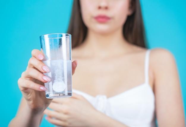 Junge frau, die pille gegen kopfschmerzen nimmt. brunette, der eine pille mit einem glas wasser nimmt frau, die medikamente einnimmt, um kopfschmerzen zu lindern. brünette nimmt ein paar pillen, hält ein glas wasser, isoliert auf blau