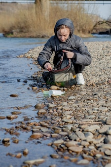 Junge frau, die plastikmüll vom strand sammelt und ihn für recycling in schwarze plastiktüten steckt. reinigungs- und recyclingkonzept.