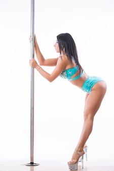 Junge frau, die pole dance fitness lokalisiert auf weißem hintergrund ausübt