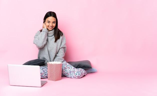 Junge frau, die popcorn isst, während sie einen film auf dem lachenden laptop sieht